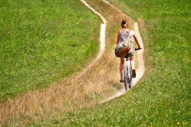 žena jedoucí na kole v přírodě